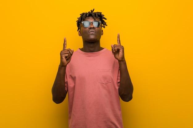Młody przypadkowy murzyn jest ubranym okulary przeciwsłonecznych wskazuje do góry nogami z rozpieczętowanym usta.