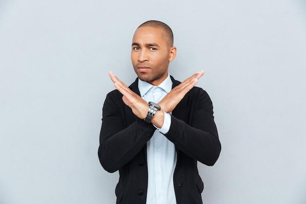 Młody przystojny afrykański mężczyzna pokazując znak stop z ręką na białym tle