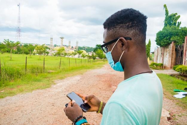 Młody przystojny afrykański mężczyzna siedzący na zewnątrz, noszący maskę na twarz, aby zapobiec, zapobiec, zapobiec wybuchowi epidemii w społeczeństwie podczas obsługi telefonu komórkowego