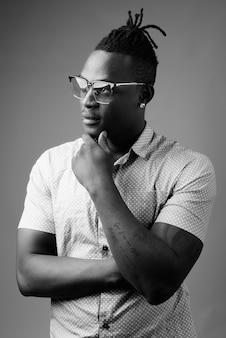 Młody przystojny afrykański mężczyzna z kenii na szarej ścianie w czerni i bieli