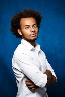 Młody przystojny afrykański mężczyzna z skrzyżowanymi rękami nad błękitną ścianą.