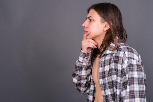 Młody przystojny androgyniczny mężczyzna hipster z długimi włosami na szarej ścianie