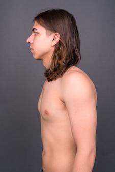 Młody przystojny androgyniczny mężczyzna z długimi włosami bez koszuli na szarej ścianie