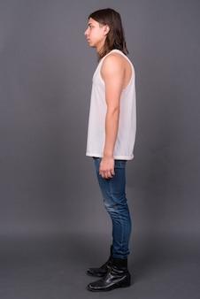Młody przystojny androgyniczny mężczyzna z długimi włosami na szarej ścianie