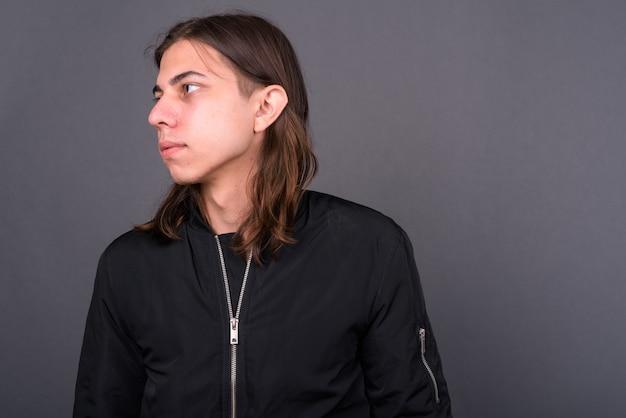 Młody przystojny androgyniczny mężczyzna z długimi włosami, ubrany w kurtkę na szarej ścianie