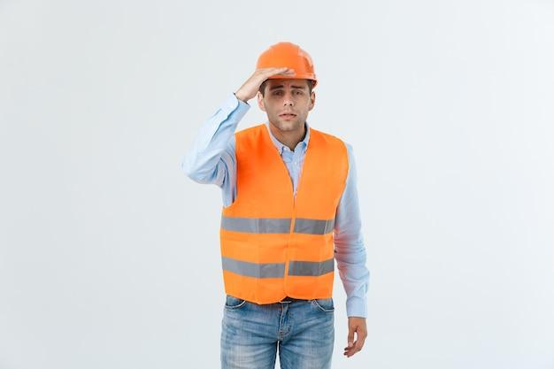 Młody przystojny architec mężczyzna z noszeniem hełmu ochronnego na na białym tle z ręką nakrywającą głowę patrząc na coś.