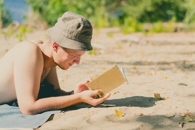 Młody przystojny atrakcyjny mężczyzna w panamie, leżąc na piaszczystej plaży i czytając książkę w letni dzień