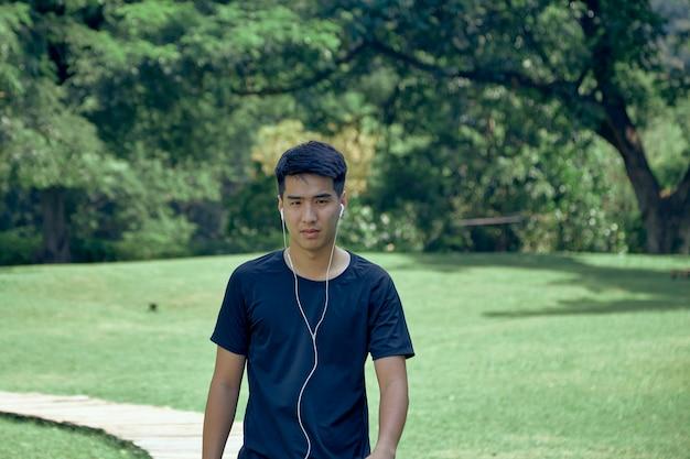 Młody przystojny azjata ćwiczeń w parku na sobie urządzenie do monitorowania kondycji