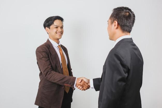 Młody przystojny azjatycki biznesmen podaje uścisk dłoni z partnerem