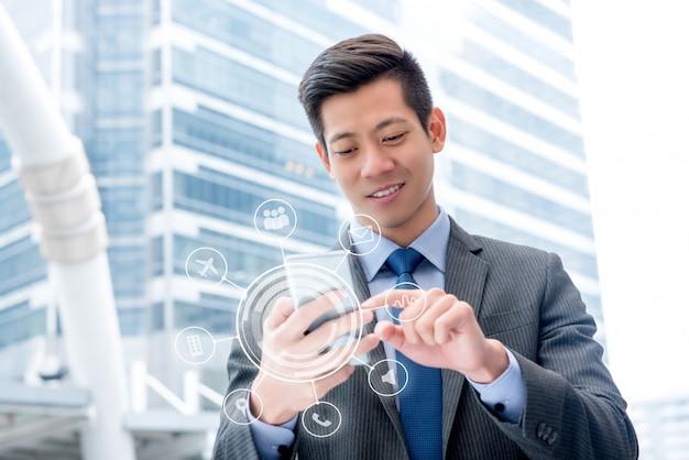 Młody przystojny azjatycki biznesmen używa telefon komórkowego