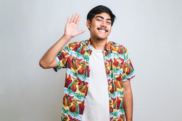 Młody przystojny azjatycki chłopak ubrany w białą koszulkę stojącą na białym tle zrzekanie się witania szczęśliwy i uśmiechnięty, przyjazny gest powitalny