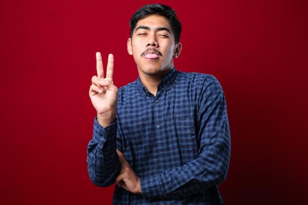 Młody przystojny azjatycki facet ubrany w zwykłą koszulę stojący na czerwonym tle robi symbol pokoju z palcami nad twarzą, uśmiechając się wesoło pokazując zwycięstwo