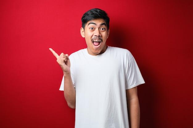 Młody przystojny azjatycki mężczyzna jest ubranym białą koszulkę na czerwonym tle z dużym uśmiechem na twarzy; wskazując palcem ręki na bok patrząc w kamerę.