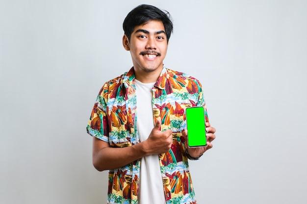 Młody przystojny azjatycki mężczyzna pokazuje zielony ekran smartfona na białym tle na białym tle, bardzo szczęśliwy, wskazując ręką i palcem w bok