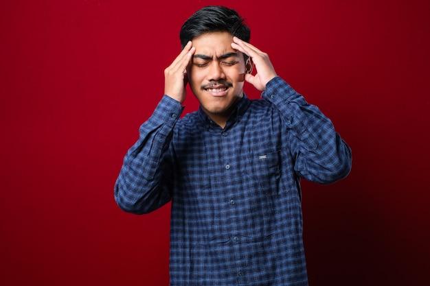 Młody przystojny azjatycki mężczyzna ubrany dorywczo koszula stojący na na białym tle czerwonym tle z ręką na głowie na ból głowy, ponieważ stres. cierpi na migrenę.