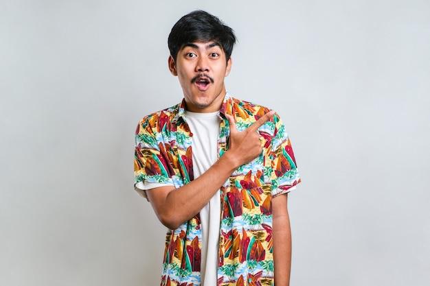 Młody przystojny azjatycki mężczyzna ubrany na co dzień koszulę na białym tle z dużym uśmiechem na twarzy; wskazując palcem ręki na bok patrząc w kamerę.