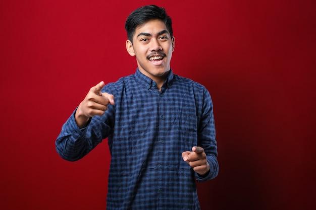 Młody przystojny azjatycki mężczyzna ubrany na co dzień w koszulę stojący na czerwonym tle, wskazujący palcami na ciebie i kamerę, uśmiechnięty pozytywnie i wesoło