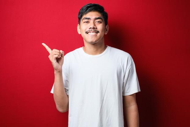 Młody przystojny azjatycki mężczyzna ubrany w białą koszulkę na czerwonym tle z dużym uśmiechem na twarzy; wskazując palcem ręki na bok patrząc w kamerę.