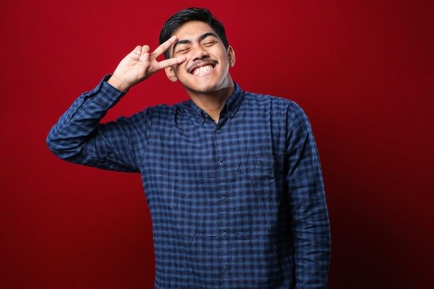 Młody przystojny azjatycki mężczyzna ubrany w zwykłą koszulę stojący na czerwonym tle robi symbol pokoju palcami nad twarzą, uśmiechając się wesoło pokazując zwycięstwo