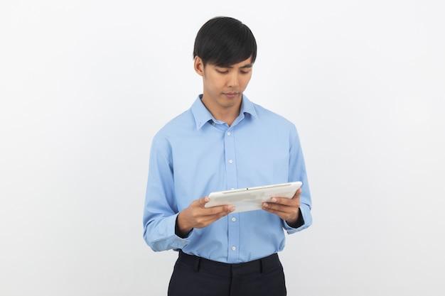 Młody przystojny azjatykci biznesowy mężczyzna bawić się i patrzeje pastylka komputer z ono uśmiecha się
