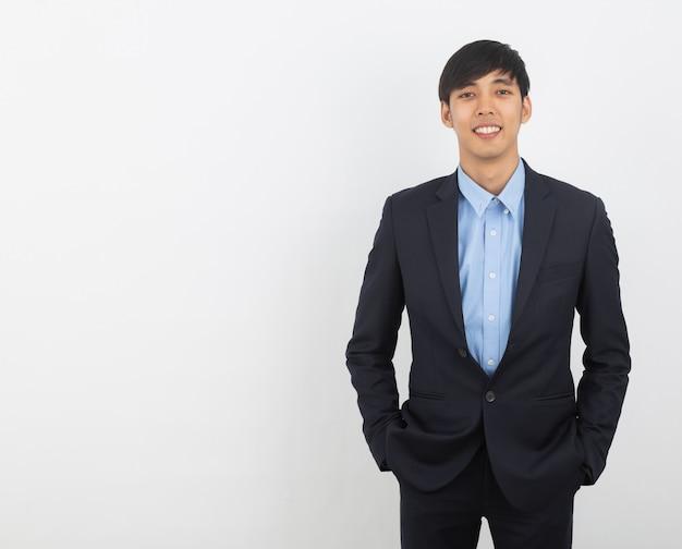 Młody przystojny azjatykci biznesowy mężczyzna patrzeje kamera odizolowywająca na bielu