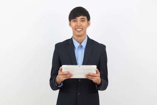 Młody przystojny azjatykci biznesowy mężczyzna używa pastylkę