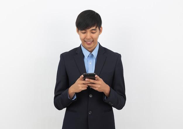Młody przystojny azjatykci biznesowy mężczyzna używa smartphone