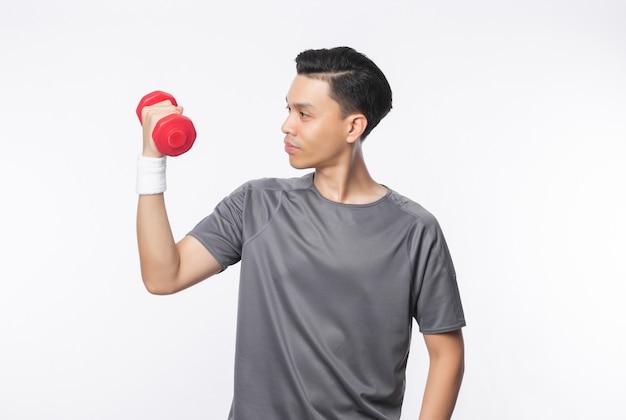 Młody przystojny azjatykci mężczyzna ćwiczy z dumbbells w sportów strojach