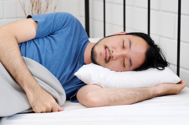 Młody przystojny azjatykci mężczyzna dosypianie na białej pigułce w łóżku, ludzie stylu życia