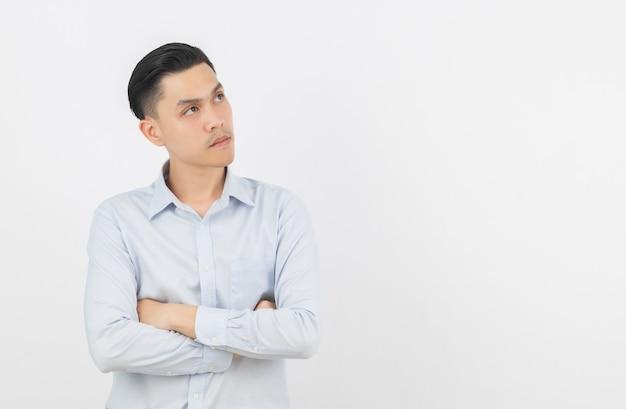 Młody przystojny azjatykci mężczyzna myśleć pomysł podczas gdy przyglądający z rękami krzyżować up