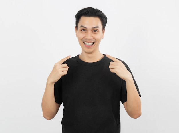 Młody przystojny azjatykci mężczyzna ono uśmiecha się z brasami i patrzeje kamerę z palcowy wskazywać odizolowywam