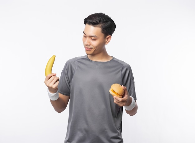 Młody przystojny azjatykci sporta mężczyzna mienia banan i hamburger
