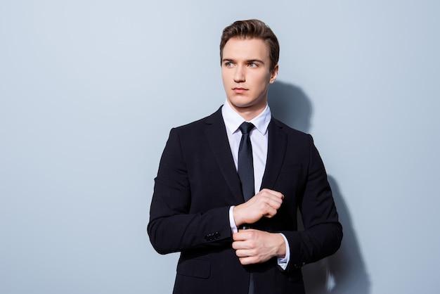 Młody przystojny bankier biznesmen w garniturze naprawia jego spinki do mankietów, stoi na czystej przestrzeni światła. taki dojrzały i męski, gorący i pewny siebie