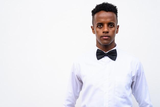 Młody przystojny biznesmen afryki na sobie muszkę na białym tle