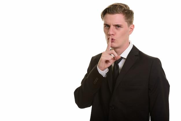 Młody przystojny biznesmen blondynka w garniturze z palcem na ustach