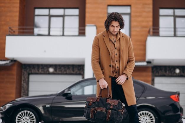 Młody przystojny biznesmen chodzenie z domu do swojego samochodu