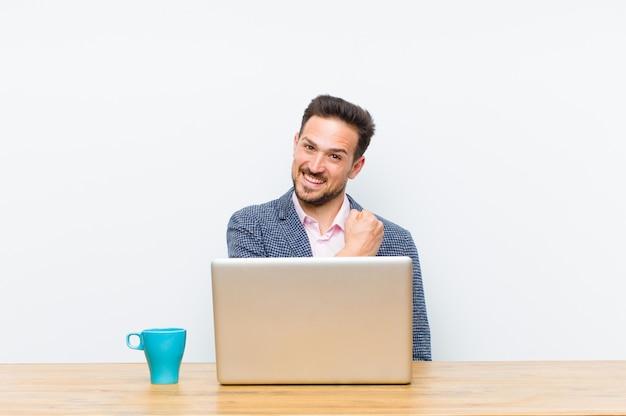 Młody przystojny biznesmen czuje się szczęśliwy, pozytywny i udany, zmotywowany, gdy stoi przed wyzwaniem lub świętuje dobre wyniki