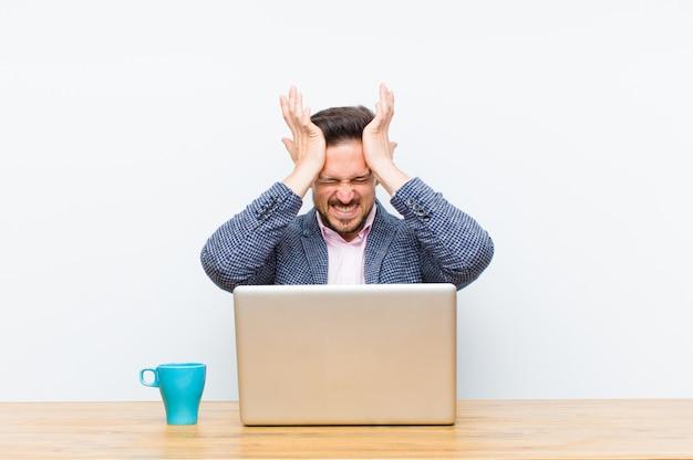 Młody przystojny biznesmen czuje się zestresowany i niespokojny, przygnębiony i sfrustrowany bólem głowy, podnosząc obie ręce do głowy
