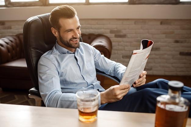 Młody przystojny biznesmen czyta czasopismo w swoim własnym biurze. siada przy stole i uśmiecha się. pozytywny wesoły człowiek posiada dziennik. kieliszek i prafen whisky na stole.
