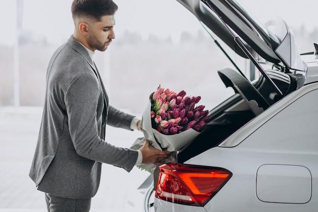 Młody przystojny biznesmen dostarczający bukiet pięknych kwiatów