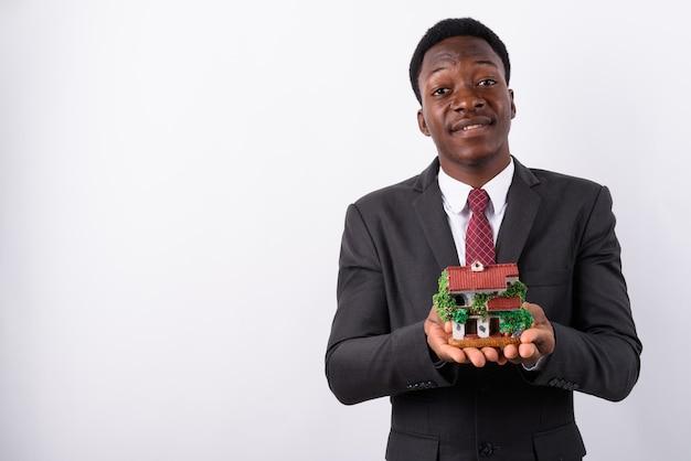 Młody przystojny biznesmen gospodarstwa figurkę domu przed białym