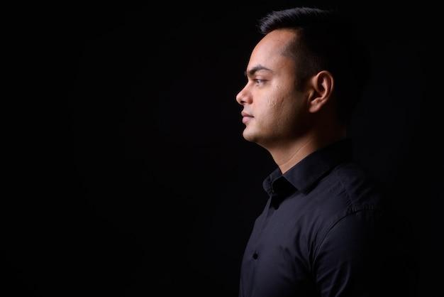Młody przystojny biznesmen indyjskich przeciw czarnej ścianie