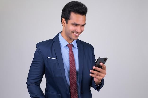 Młody przystojny biznesmen indyjskich ubrany w garnitur na białym tle