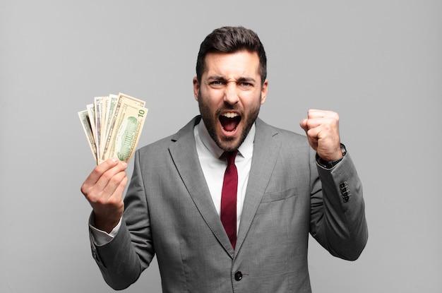Młody przystojny biznesmen krzyczy agresywnie z gniewnym wyrazem twarzy lub z zaciśniętymi pięściami świętuje sukces. koncepcja rachunków lub pieniędzy