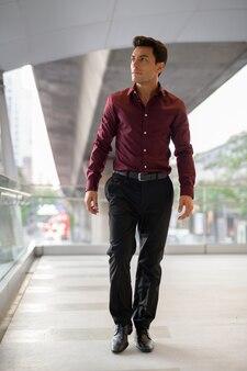 Młody przystojny biznesmen latynoski myślenie i chodzenie po kładce