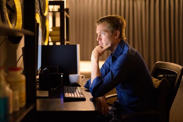 Młody przystojny biznesmen myśli podczas pracy w godzinach nadliczbowych w domu późno w nocy