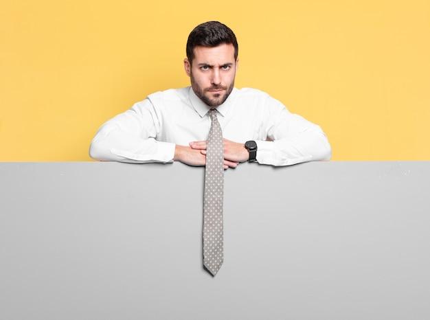 Młody przystojny biznesmen na szarej tablicy