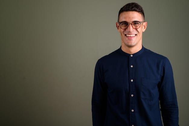 Młody przystojny biznesmen noszenie okularów przed kolorowym ba