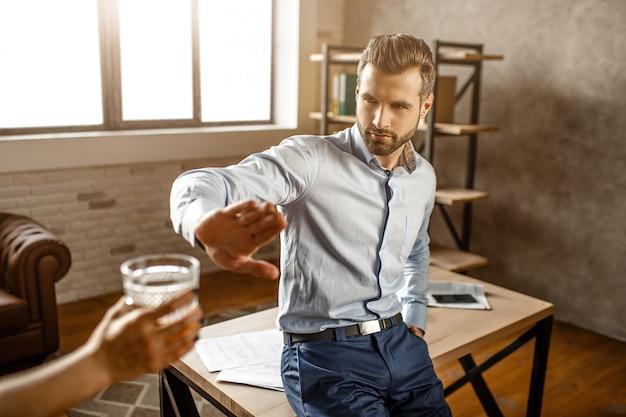 Młody przystojny biznesmen opierać się stołem w jego własnym biurze. pokazuje ludzkiemu znakowi stopu kieliszek whisky. facet odmawia.