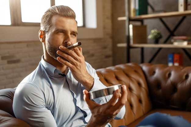 Młody przystojny biznesmen pali cygaro w jego własnym biurze. siada na kanapie i trzyma popielnik. pewny siebie i seksowny. światło dzienne.